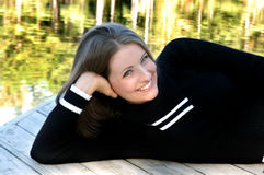 Dock Relaxing by Lakeside. Young teen leans on a wooden dock beside a lake.  She has on a black sweater with white trim Stock Image