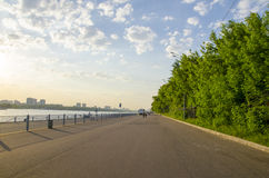 The dock by the river. The road goes along the river along the pier Royalty Free Stock Image