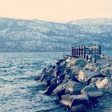 Dock and rocks on lake in winter Stock Image