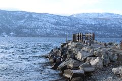 Dock and rocks on lake in winter Royalty Free Stock Photo