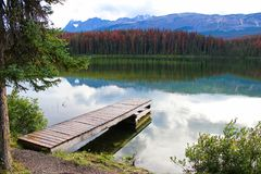 A dock beside a rocky mountain lake royalty free stock images