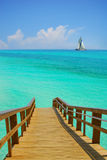 Dock and Sailboat. Wooden dock leading to turquoise sea with sailboat in distance Royalty Free Stock Images