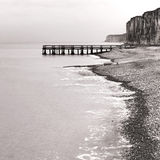 Dock at Sea and Rocky Cliffs on Seaside Rock Beach. Loading dock jetty extending at sea and rocky cliffs on a seaside rocky beach on the English Channel in Stock Photography
