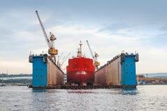 Dock sec bleu de flottement avec le bateau-citerne rouge sous la réparation Photo stock