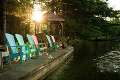Dock side muskoka chairs. Serene sunny morning, dockside filled with colourful muskoka chairs ..  Up North, beautiful Ontario waters Stock Photos