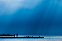 Dock in silhouette with people and rays of light Royalty Free Stock Photos