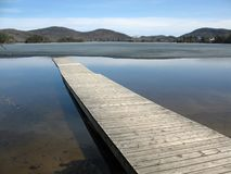 Dock in spring. A long gray dock juts diagonally into a pristine, half-frozen mountain lake Stock Photos