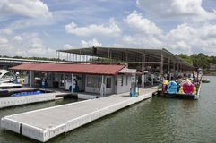 Dock and store gas station at luxury marina that has private patios for boat stalls - American flags flying and restaurant in stock image