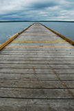 Dock on Stormy Day. A weathered wooden dock vanishes into the horizon on a cloudy, stormy day Royalty Free Stock Photos