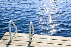 Dock on summer lake with sparkling water. Dock and ladder on calm summer lake with sparkling water in Ontario Canada stock photography