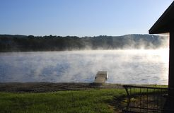 Dock at sunrise with mist on lake stock images