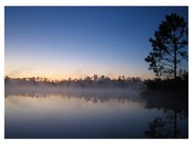Dock Sunrise with white border. Dock at sunrise with fog, taken in Pace, Florida, October, 2005 royalty free stock images