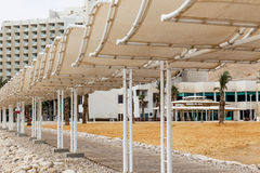 Dock and sunshade on hotel background. Wooden dock and sunshades on white hotel and yellow sand background Royalty Free Stock Images