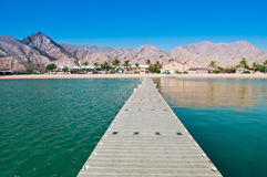 The Dock to Paradise. A look at the rugged coastline of Oman and a resort from the end of the dock Stock Photography