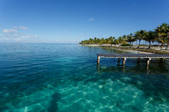 Dock on tropical island and turquoise waters. Dock on tropical island loaded with palm trees highlight pattern of sunlight in beautiful turquoise waters of the Stock Image