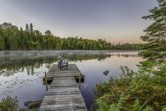 Dock und Stühle auf einem See bei Sonnenuntergang Stockfotos