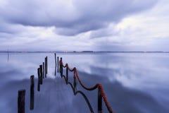 Dock verschwinden in das reflektierende Wasser des Sees lizenzfreie stockfotos