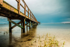 Dock on the water. Long dock starting from the beach going out to the gulf of Mexico during low tide on a cloudy day Stock Photography