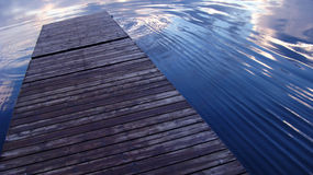 Dock and water ripples. A quay or dock and water ripples with cloud and sky reflection royalty free stock images