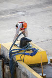 Dock Worker Attaching Ropes to a Bollard Stock Image