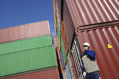 Dock worker and containers. Worker with stacks of cargo containers in background Royalty Free Stock Image