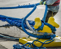 Dock worker pulling on ropes Royalty Free Stock Photo