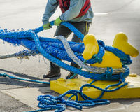 Dock worker pulling on ropes Royalty Free Stock Photos