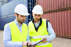 Dock worker and supervisor checking containers data on tablet Royalty Free Stock Images