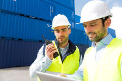 Dock worker and supervisor checking containers data on tablet Royalty Free Stock Image