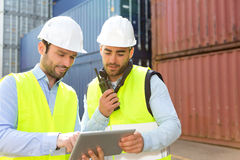 Dock worker and supervisor checking containers data on tablet Royalty Free Stock Photo