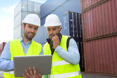 Dock worker and supervisor checking containers data on tablet Stock Photos