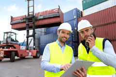 Dock worker and supervisor checking containers data Stock Image