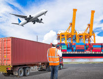 Dock worker talking on the walkie-talkie for controlling loading. Container in an industrial harbor with truck transport container and cago plane flying above Royalty Free Stock Photography