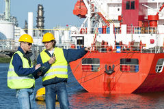 Dock workers. Two dockers at work, wearing safety vests hand hard hats, in frond of a red fire boat at a petrochemical harbor Royalty Free Stock Photo