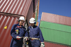 Dock workers and containers. Workers with stacks of cargo containers in background Stock Photo