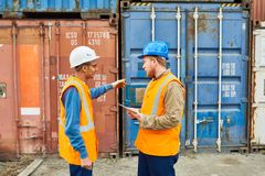 Dock Workers Discussing Shipping. Side view portrait of two dock workers wearing hardhats talking to each other standing against cargo containers Royalty Free Stock Photography