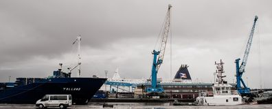 Dock working. A ship in port to be unloaded with a ferry in the background Royalty Free Stock Photos