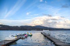 Dock at Yamanaka lake, Yamanashi, Japan. Wooden dock, swan boat and beautiful blue sky at Yamanaka lake, Yamanashi prefecture, Japan Stock Photography