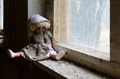 Docka på fönsterbräda i övergett dagis i förstörd by av Kopachi, Tjernobyl uteslutandezon, Ukraina royaltyfria bilder