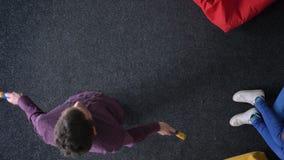 Docka som överkant-skjutas av repet och kvinnan för man som det hoppa spelar med bollen som sitter på mångfärgad mjuk påse stock video