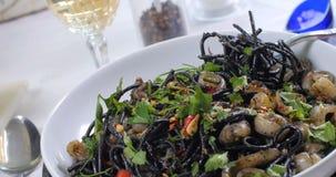 Docka som panorerar sikt av läcker pasta med tioarmade bläckfiskar (bläckfisk) och färgpulver stock video