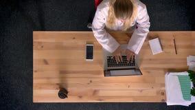 Docka som skjutas av överkant ner sikt av denklädde kvinnan i vitt skjortaarbete genom att använda bärbara datorn i regeringsstäl lager videofilmer