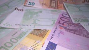 Docka som skjutas av eurosedelbakgrund som överst staplas av de Glidning till och med europengarsedlar, hög av pengar, kassa, stock video