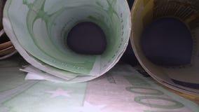 Docka som skjutas av eurosedlar rullande i rör Glidning till och med europengarsedlar, h?g av pengar, kassa, bunt av r?kningar arkivfilmer