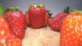 Docka som skjutas av r?da saftiga jordgubbar p? tr?bakgrund S?t sk?rdad jordgubbebakgrund, sund matlivsstil arkivfilmer