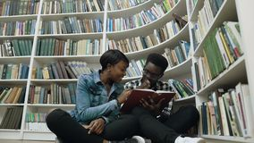 Docka som skjutas av ung afrikanman och kvinnliga studenter som sitter på golvet nära bokhyllor medan läsebok in lager videofilmer