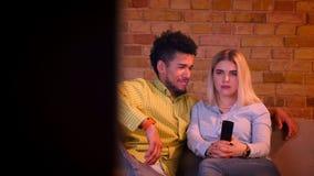 Docka som skjutas av ung afrikansk grabb med hans hållande ögonen på TV för blond caucasian flickvän i hemtrevlig hem- atmosfär lager videofilmer