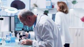 Docka som skjutas av vuxen doktor eller forskaren som använder ett mikroskop arkivfilmer