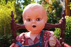 dockan sitter i en highchair Arkivfoto