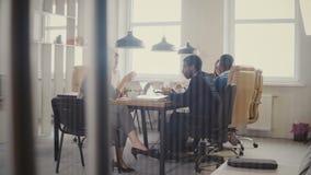 Dockan sköt av lycklig affärspartnerdiskussion i modernt kontor Multietniska framstickanden samarbetar på affärsprojektet 4K arkivfilmer